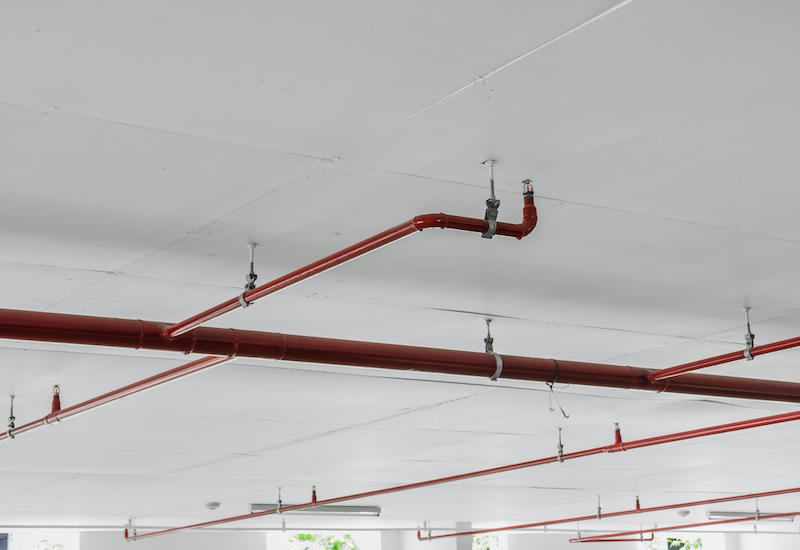 A close-up shot of a Fire sprinkler and red pipe on white ceiling background