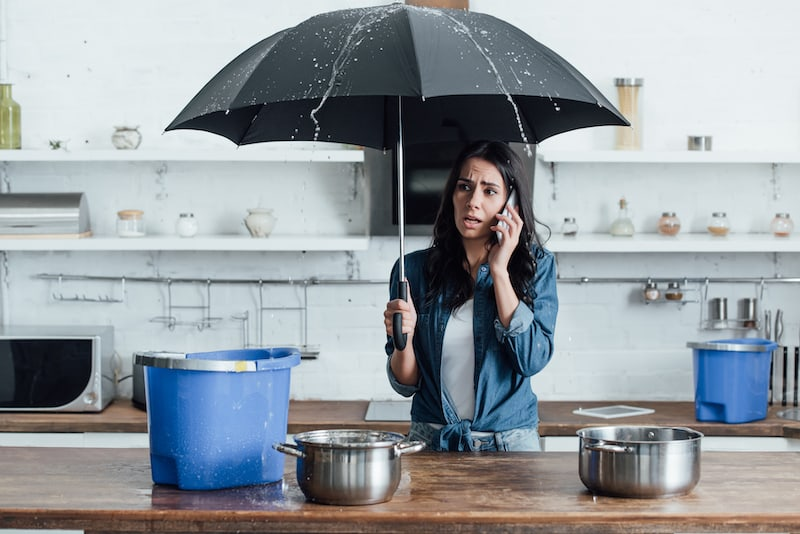 a lady holding and umbrella as her firesprinkler system activates